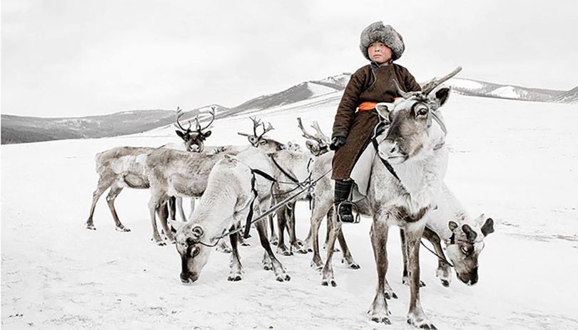Tsaatan boy riding a reindeer